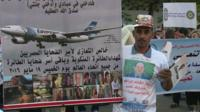 Man holding poster with EgyptAir and pictures of victims