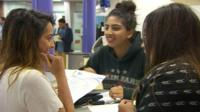 Three seated students with A-Level results in hand