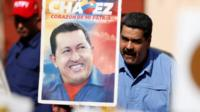 President Maduro and a placard with an image of Hugo Chavez
