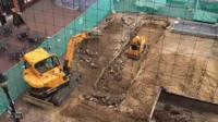 Diggers carving out trenches for archaeological dig