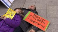 "A man and child lay down as part of the ""die-in"""