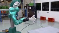 A robot holding a spray bottle