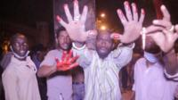 Sudan protesters hold up hands covered in blood