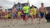 Swimmers running into the sea in Guernsey
