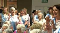 A choir, made up of people with dementia and their carers, sings for passengers at Luton Airport.