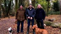 Three men looking into the camera on a dog walk with three dogs in the woods