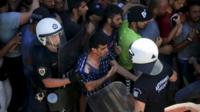Migrants clash with riot police