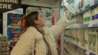 Woman choosing non-dairy milk from a shelf
