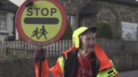 Lollipop lady holding up a Stop sign