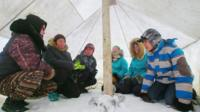 A class of several students gather in a tent, with snow for the ground