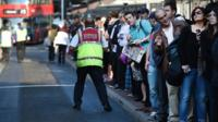 Commuters try to board buses at Victoria Station in London