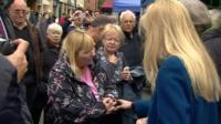 Woman speaking to Theresa May and Nicola Blackwood