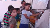 Children in Gaza get water from a communal supply