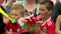 Two young fans in Wales football shirts with Wales flag
