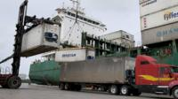 A container ship is loaded with shipping containers at Port Everglades, in Fort Lauderdale, Florida