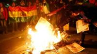 Protesters burn newspapers during a march in La Paz