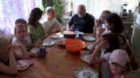 Children and adults sitting around a table about to eat lunch