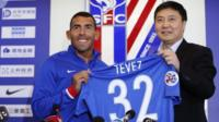 Carlos Tevez (L) holds his new jersey at his first press conference after joining Shanghai Shenhua