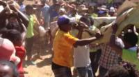 People carrying a shrouded corpse and dancing in Madagascar