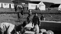 People carrying delivery supplies to houses in the Canadian Arctic