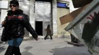 People walk past a burned bank branch under reconstruction following recent violent clashes in central Athens.
