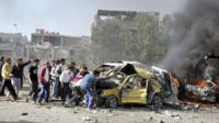 People and security personnel try to remove a car from an explosion site in Damascus