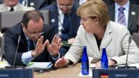 French President Francois Hollande speaks with German Chancellor Angela Merkel