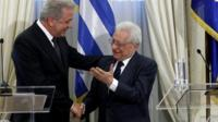 Newly appointed Greek Foreign Minister Dimitris Avramopoulos (left) shakes hands with outgoing Foreign Minister Petros Molyviatis