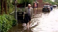 A man walks in a flooded road
