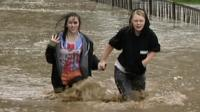 Girls wade through deep water
