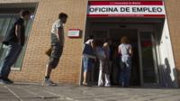 Jobseekers queue up outside a job centre in Madrid