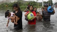 Residents wade through water