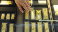 In a picture taken on March 2, 2011 a Chinese sales assistant arranges gold bars at a gold jewellery shop in Hefei.