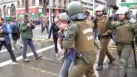 A Chilean protester being taken away by police