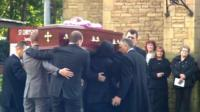 Coffin carried into church