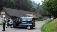 French gendarmes block the road leading to the scene where four people died in a shooting at a parking near the Annecy Lake, eastern France, on Wednesday