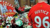 Floral tributes and man wearing 'Justice 96' shirt