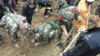 Police search for victims of the landslides in Yunnan province