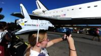 Girl wearing shuttle hat watches shuttle drive by
