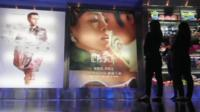 People at a Chinese cinema, looking at posters