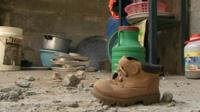 Child's boot and household items in rubble
