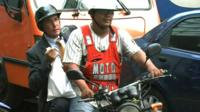 A taxi driver and his passenger on a motorbike taxi