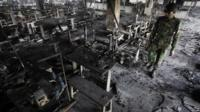 A soldier inspects the gutted factory