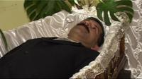 Man lying in coffin