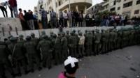 Demonstrators and security forces line concrete barrier