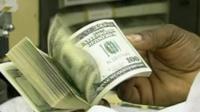 Man flicking through bundle of $100 bills