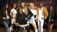 Danielle (L) , Este (C) and Alana Haim stand with Abba waxworks