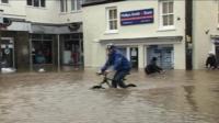 Cyclist rides through flood water in Braunton