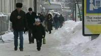 People walk on snow covered street in Ukraine