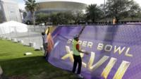 Two men secure a screen over a fence that surrounds the Mercedes-Benz Superdome